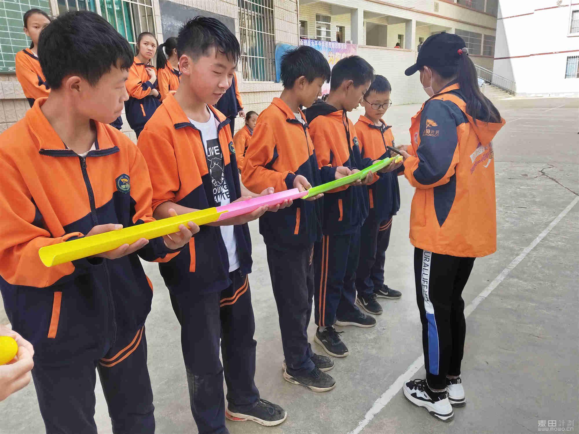 这个游戏叫千里传珠,孩子们小心翼翼,齐心协力的把珠子传到指定地方。